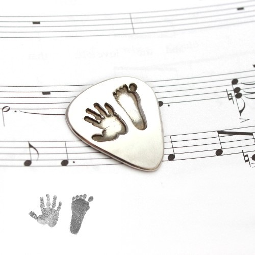 silver hand and footprint guitar pick